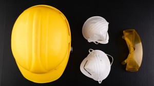 Helmet And Protective Mask On A Dark Table. Protection Against Adverse Conditions At Work. Dark Background.