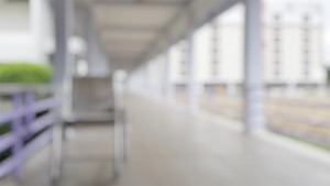 Blur Abstract Background Of Corridor In Clean Hospital With Patient Wheelchair In Hospital. Blurry Wheel Chair For World Disability Day. Defocus Lobby And Waiting Area.