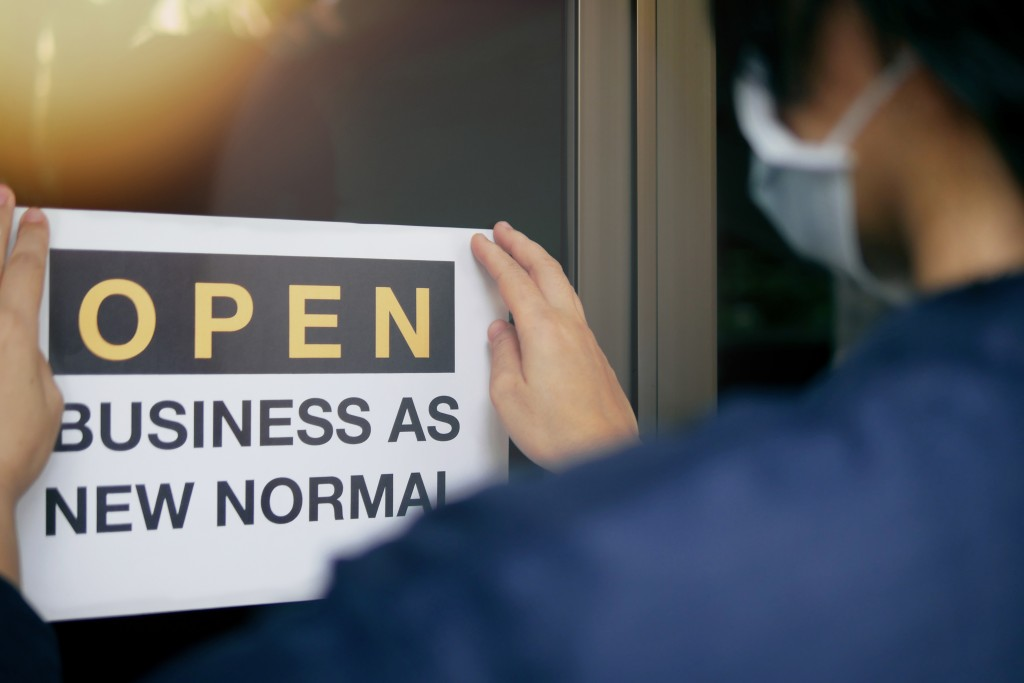 """Reopening For Business Adapt To New Normal In The Novel Coronavirus Covid 19 Pandemic. Rear View Of Business Owner Wearing Medical Mask Placing Open Sign """"open Business As New Normal"""" On Front Door."""