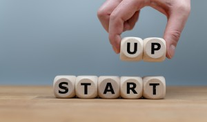 """Cubes Form The Words """"start Up"""" While To Fingers Lift The Letters """"up"""" In The Air. Cubes Are On A Wooden Table In Front A Grey Background."""