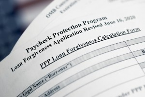 Selective Focus Photo Of Paycheck Protection Program Loan Forgiveness Application Form Revised, On A Background Of United States Flag. Paycheck Protection Program New Round.