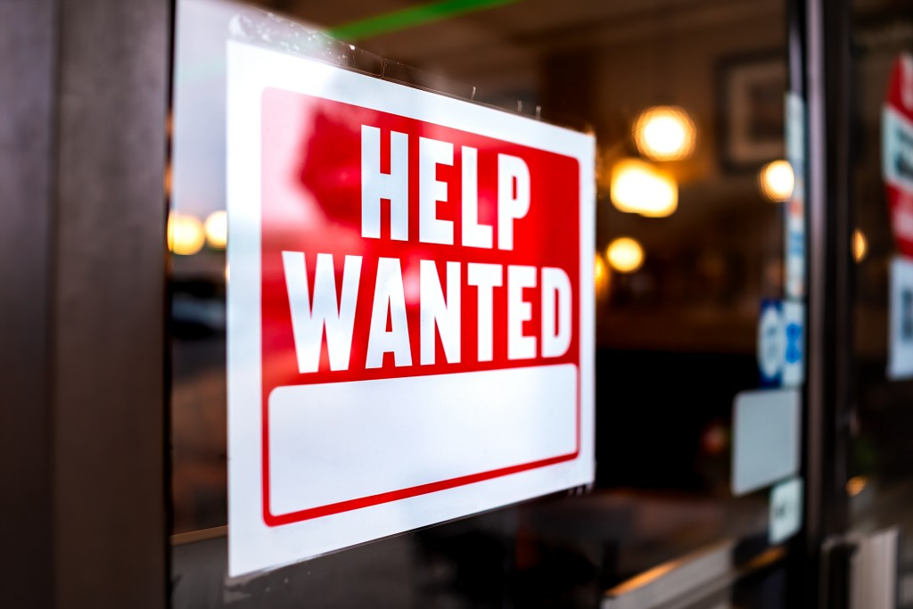 Sign Text Closeup For Help Wanted With Red And White Colors By Entrance To Store Shop Business Building During Corona Virus Covid 19 Pandemic